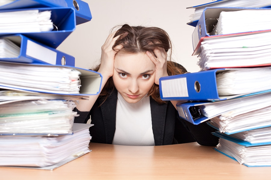 Frustrated Businesswoman With Stack Of Folders