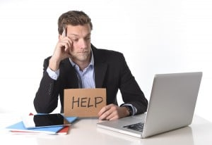 Attractive Businessman Working In Stress At Computer Holding Hel